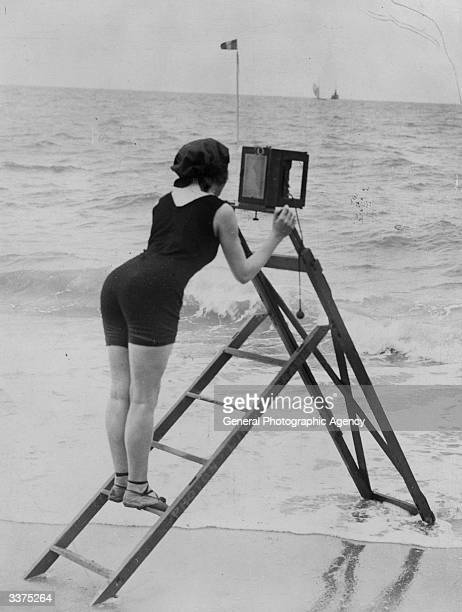 A professional photographer taking snaps of the holidaymakers on the beach at Ostend She is using a ladder to steady her camera and keep it out of...