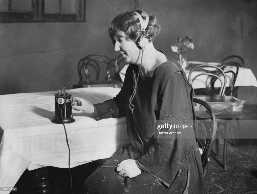 A woman listening to a crystal wireless set through headphones.