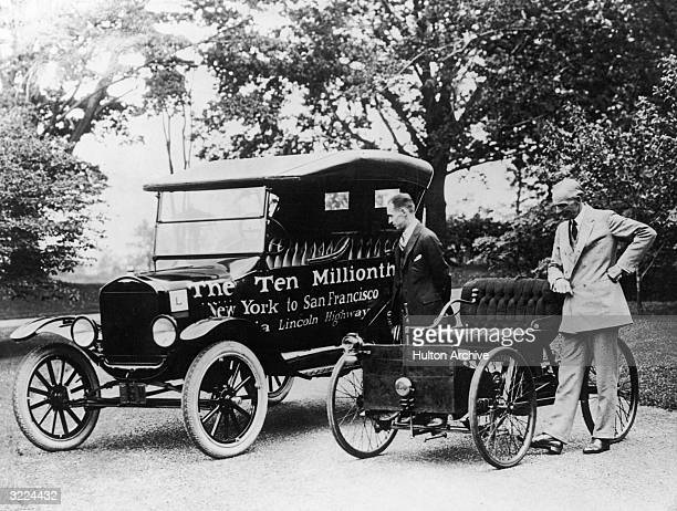 Full-length image of American industrialist and inventor Henry Ford and his son, auto executive Edsel Ford , inspecting the first and the Tenth...