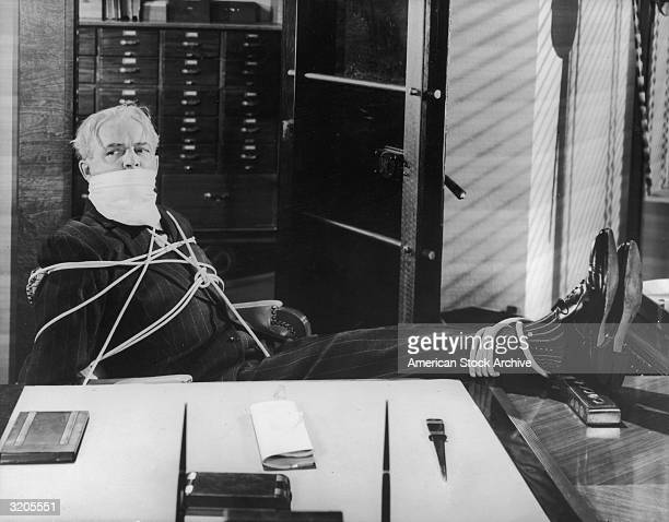 A banker sits gagged and tied up at a desk in front of an open safe during a robbery in an unidentified silent film still