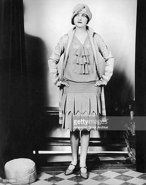 A flapper woman wearing a dress coat and cloche hat