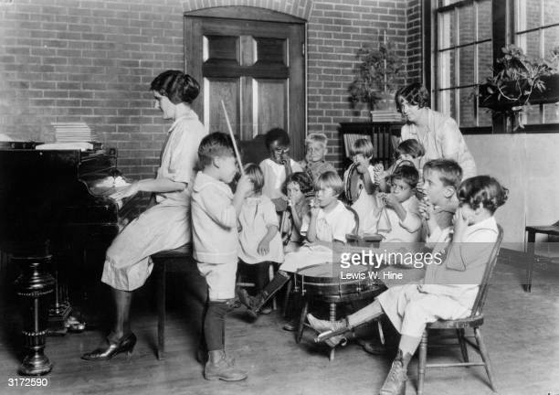 A group of young music students play various instruments including a drum tambourine triangle and kazoo along with their teacher who sits at a piano