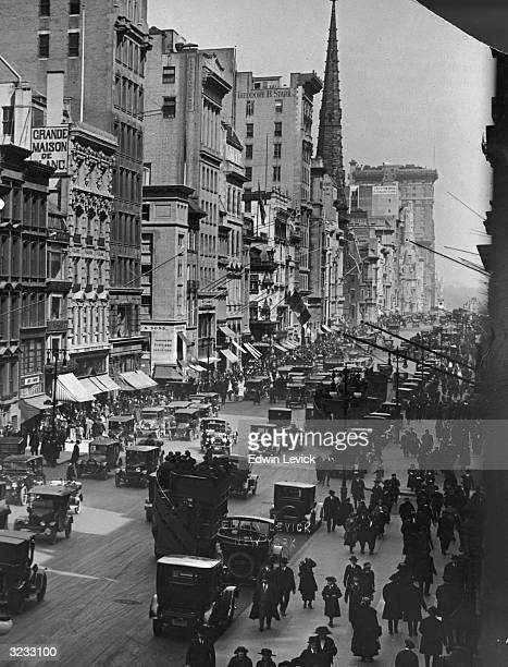 A highangle street scene of people walking down Fifth Avenue in Manhattan New York City Automobiles drive down the street as pedestrians crowd the...