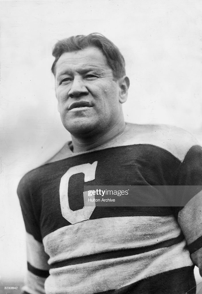 A low-angle view of athlete Jim Thorpe (1887 - 1953) wearing a Canton Bulldogs football jersey.