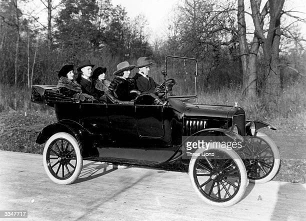 A mixed crowd go for a drive in the country in a black model 'T' Ford