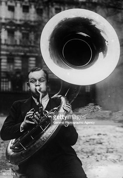 A musician practising a low note on the tuba