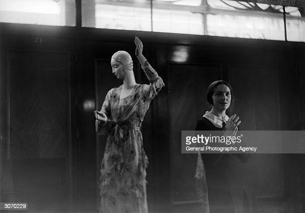 A shop assistant prepares a window dummy for display in a department store possibly Harrods