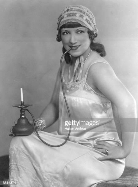 A woman in nightwear smoking a hookah pipe