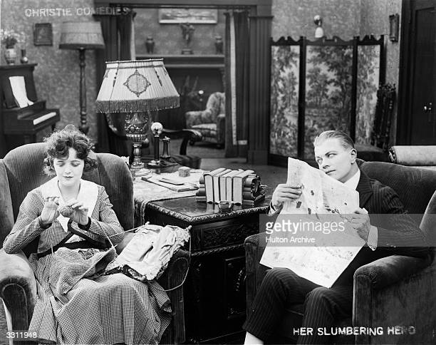 A woman knits while her husband reads the newspaper in this scene from the film 'Her Slumbering Hero' starring Bobby Vernon