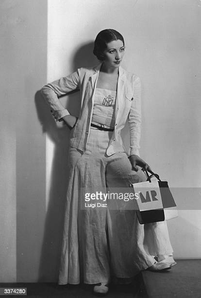 A woman modelling a white linen sailor style trouser suit with wide trouser legs and matching jacket