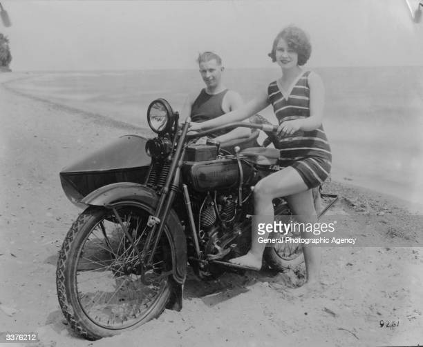 A woman on a beach in California with her Harley Davidson and boyfriend who is sitting in the side car