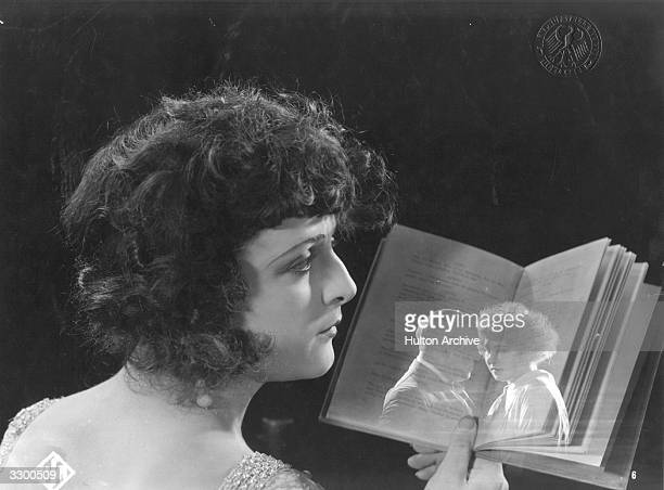 A woman remembers a past love with faces reflected onto the pages of a book she is holding in a scene from an unknown film