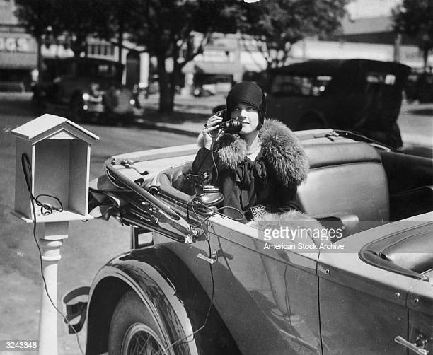 A woman sits in an automobile while talking on the telephone from a phone service stand at the Hotel Constance in Pasadena California She is wearing...