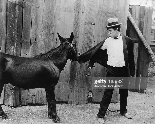 American actor and humorist Will Rogers looks behind as a mule bites his jacket in an unidentified film still