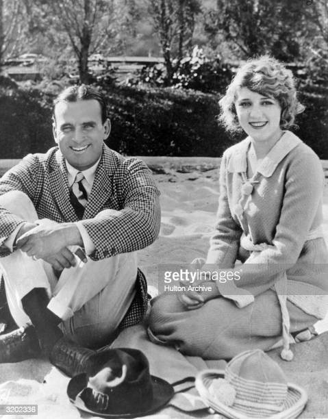 American actor Douglas Fairbanks, Sr. And his wife, Canadian-born actor Mary Pickford smile while sitting and kneeling in sand.