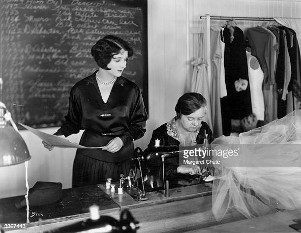 American actress Gertrude Olmstead consulting one of the wardrobe staff at the MGM studios about a new dress that is being made for her