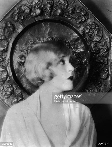 American film star Mae Murray poses in front of an ornamental plaque