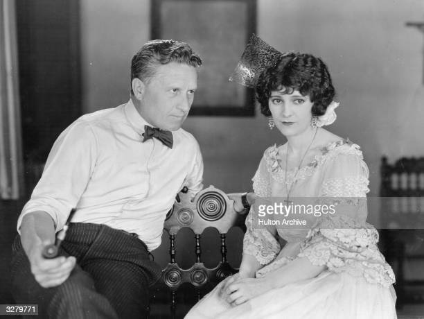 American silent movie director Fred Niblo talks to actress Edith Roberts on the set of the MGM production 'Thy Name Is Woman'
