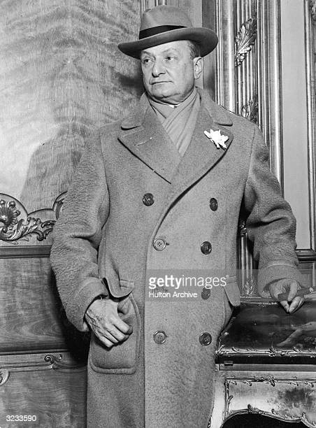 American theatrical producer Florenz Ziegfeld Jr smokes a cigar in a doublebreasted overcoat which bears his trademark white flower in its lapel He...