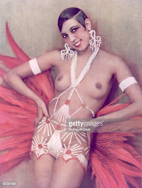 Americanborn singer dancer and Folies Bergere star Josephine Baker exposing her breasts in a cabaret costume consisting of rhinestones and feathers...