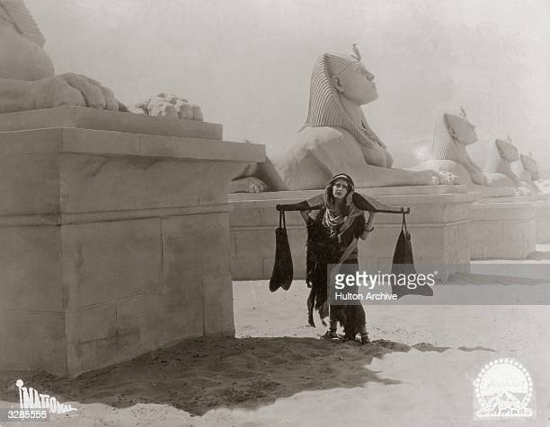 An Egyptian woman carrying a heavy burden past a row of sphinxes in a scene from the German film 'Die Zehn Gebote'