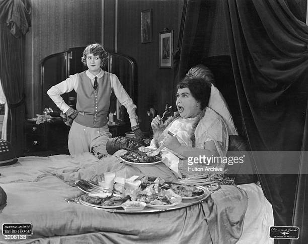 An obese woman shrieks while eating a lamb chop in bed in front of a woman dressed in a riding habit in a still from the Mermaid comedy 'His High...