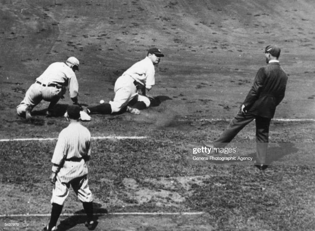 Babe Ruth (George Herman Ruth, 1895 - 1948) of the New York Yankees slides into first base after Bud Clancy of the Chicago White Sox dropped a throw.