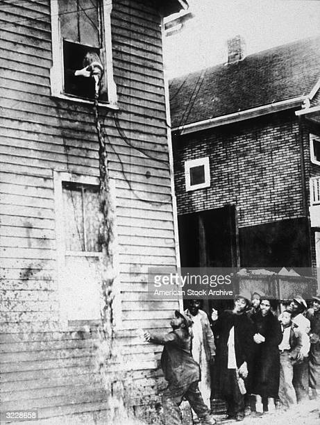 Bystanders attempt to catch in cups moonshine being poured out of a second story window by Federal agents during a raid on an illegal still.