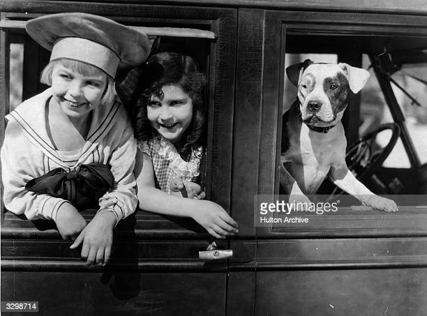 Child actors Arthur Trimble as Buster Brown and Doreen Turner as Mary Jane leaning out of a car window with their dog in the front seat in one of the...