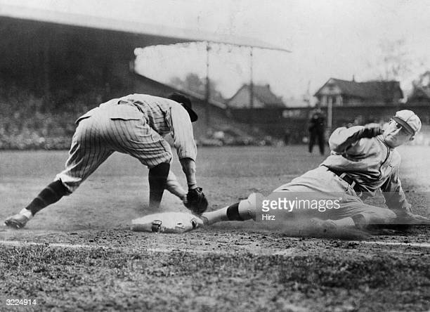 Detroit Tigers outfielder Ty Cobb slides into first base while a firstbaseman tries to tag him during a game in a stadium.