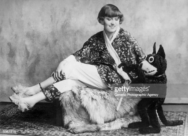 Fashion designer Dolly Tree poses in kimonostyle nightwear with a model of the cartoon character Corky the Cat