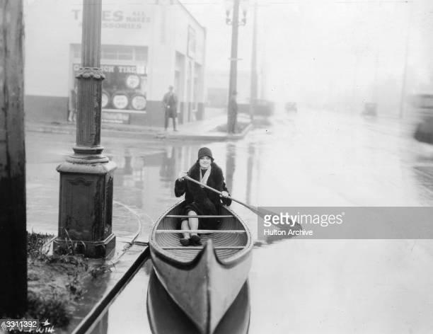 Film actress Myrna Loy paddling a canoe through a flooded street
