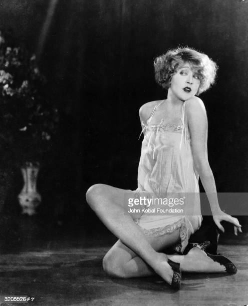 Film star Mae Murray poses in a neglige