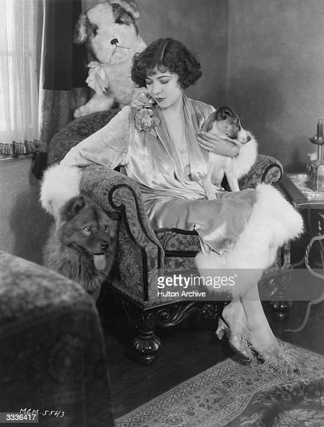 French born actress Renee Adoree sitting with a ChowChow and a Jack Russel dog