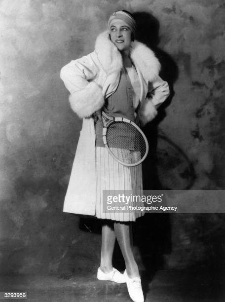 French tennis player Suzanne Lenglen modelling a new outfit, a below knee length pleated skirt and coat.
