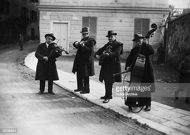 Fulllength image of four gypsy musicians playing four different string instruments on the streets of Vienna Austria