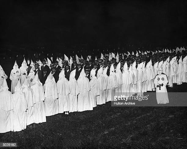 Fulllength image of men in suits and hats standing between members of the Ku Klux Klan at an initiation ceremony