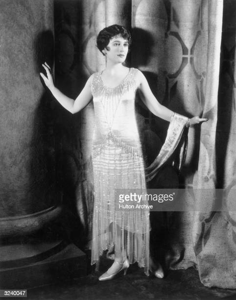 Fulllength portrait of a woman wearing a formal evening dress while standing in front of curtain