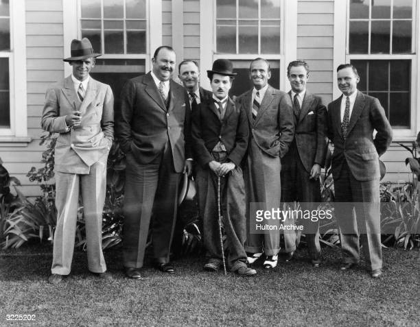 Full-length portrait of British actor and director Charles Chaplin, dressed as The Tramp, standing outdoors with actor Douglas Fairbanks Jr,...