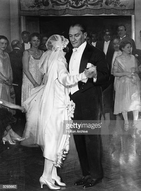 Guests clustered in a doorway watch as Mustafa Kemal Ataturk President of the Turkish Republic dances with his adopted daughter at her wedding The...