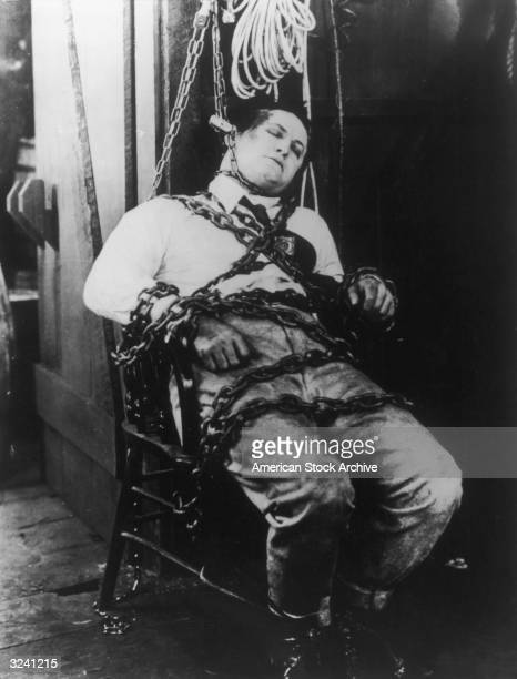 Hungarianborn magician Harry Houdini is bound to a chair with chains and shackles