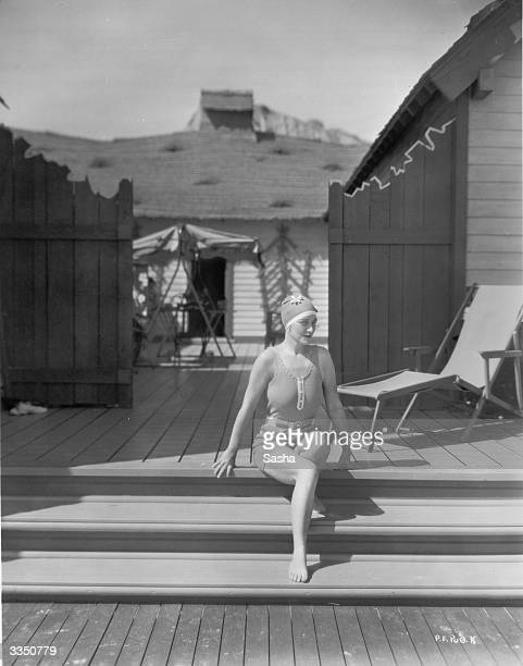 In a swimsuit and swimcap silent film star Pauline Frederick on the steps of her beach bungalow