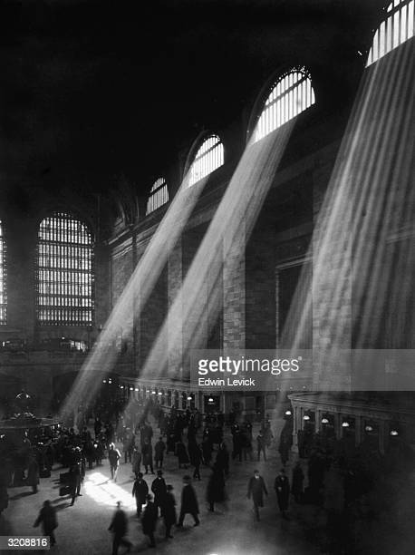 Light streams through archshaped windows as passengers pass through Grand Central Station New York City NY