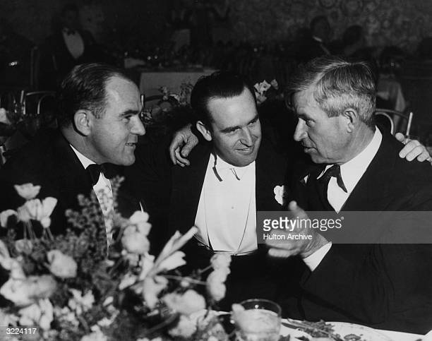 LR American film producer Hal Roach comic actor Harold Lloyd and humorist Will Rogers sit and talk at a table during an event in honor of Roach