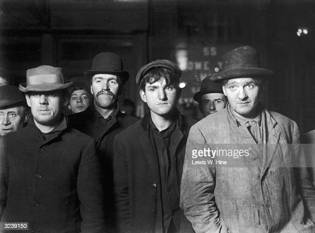 Men and boys wait in the bread line at the Bowery mission around midnight during the Depression New York City