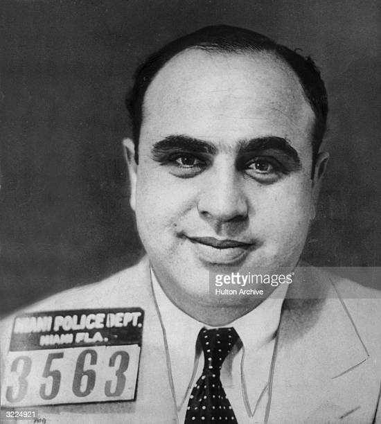 Mugshot of American gangster Al Capone smiling in a jacket and tie, Miami, Florida.