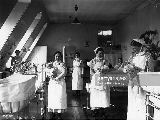 Nurses holding babies in the maternity ward of St Bartholomews Hospital London