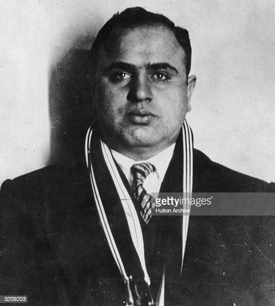 Portrait of American mafia boss Alphonse Capone , Chicago crime kingpin, wearing a suit with a striped scarf.
