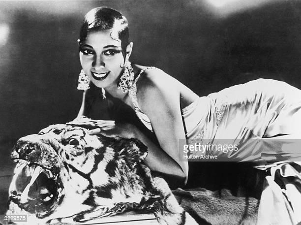 Portrait of American-born singer and dancer Josephine Baker lying on a tiger rug in a silk evening gown and diamond earrings.