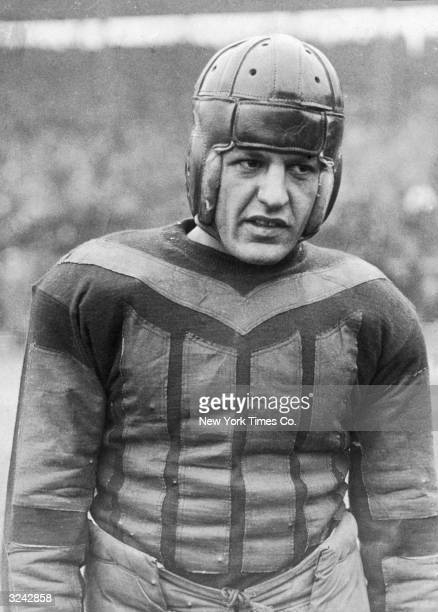 Portrait of the Chicago Bears' football player Harold 'Red' Grange wearing a helmet and football jersey at the start of his first professional game...